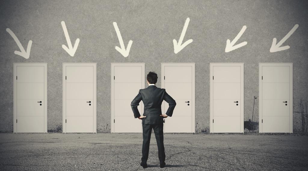 Hombre con traje enfrente de muchas puertas blancas que simulan oportunidades