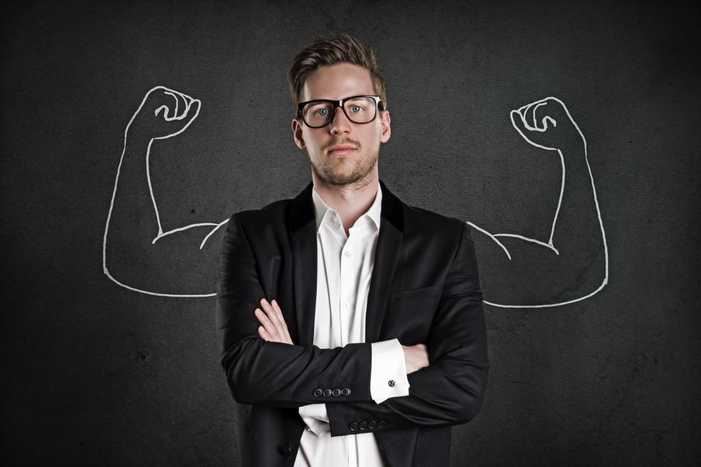 Hombre trajeado con lentes enfrente de un dibujo de unos brazos fuertes