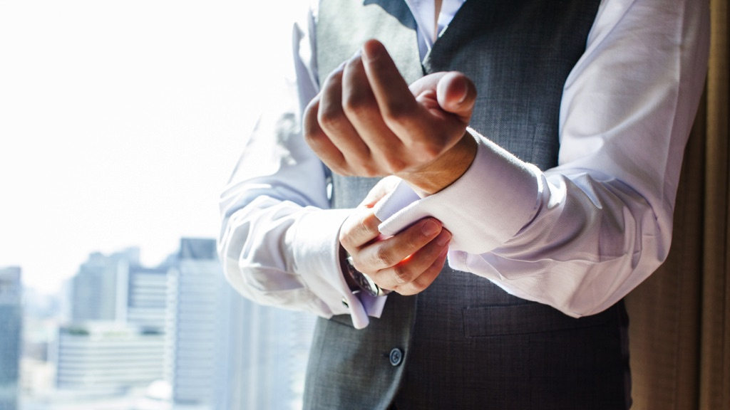 Hombre abrochándose las mancuernas de los brazos