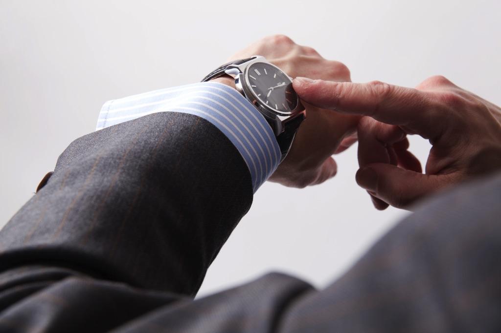 Hombre trajeado tocando su reloj con un dedo