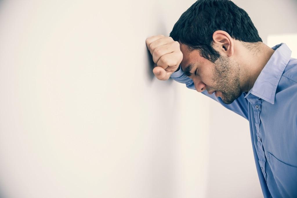 Un hombre frustrado recarga su cabeza sobre la pared
