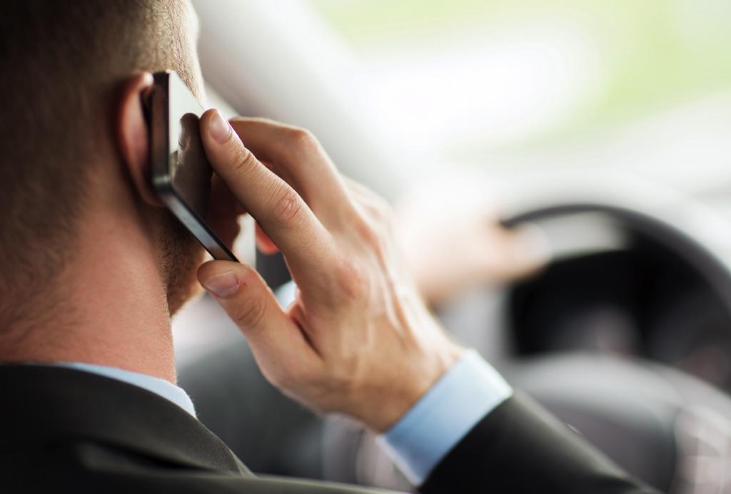 Hombre va manejando mientras habla por el celular