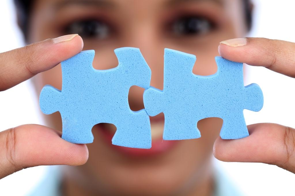 Mujer con dos piezas de rompecabezas