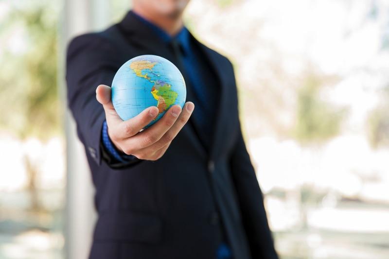 Hombre trajeado sosteniendo el mundo en su mano