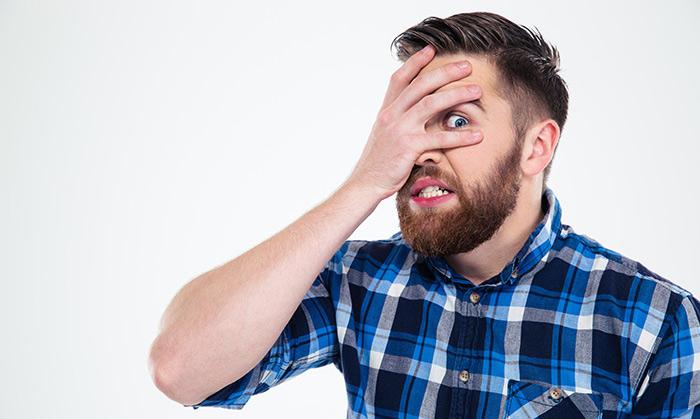Persona que acaba de cometer un error, tapándose un ojo para esconderse
