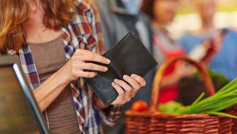 Mujer en el súper sacando su tarjeta de crédito