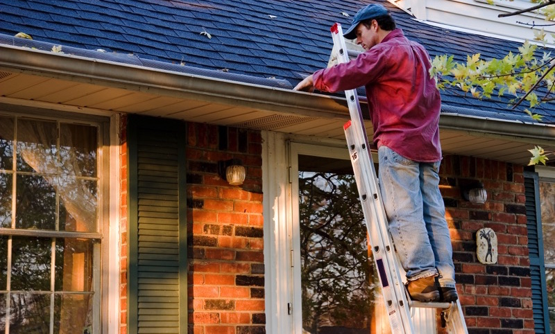 Señor en una escalera arreglando el techo