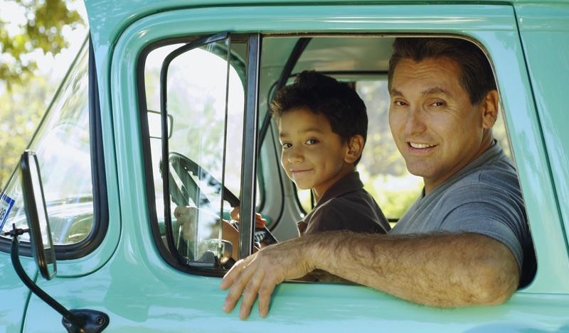 Padre e hijo sonriendo en una camioneta