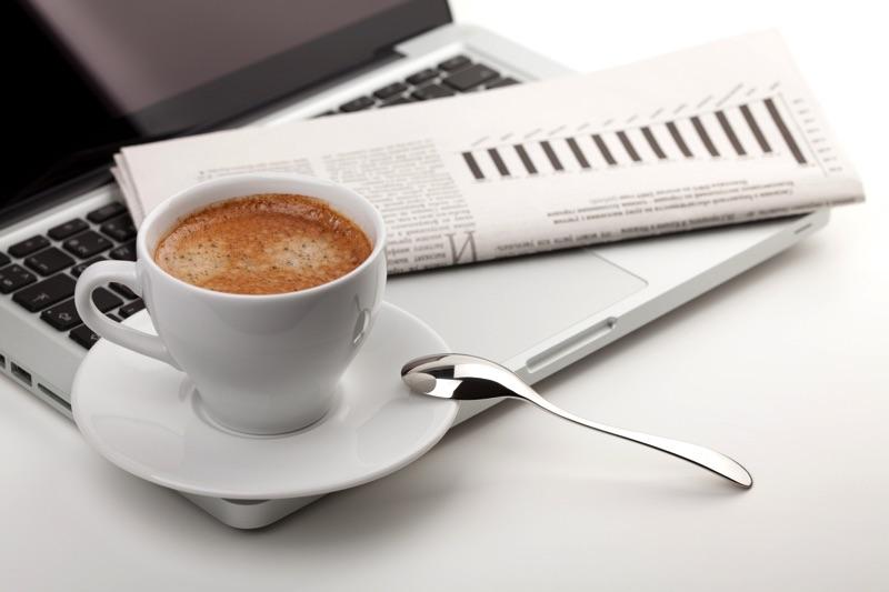 Encima de una laptop están una taza de café y una servilleta