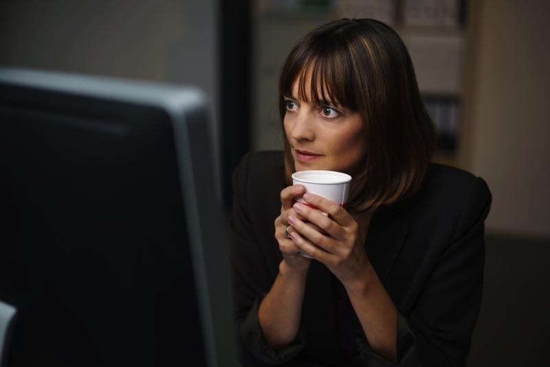Mujer enfrente de una computador con café en mano