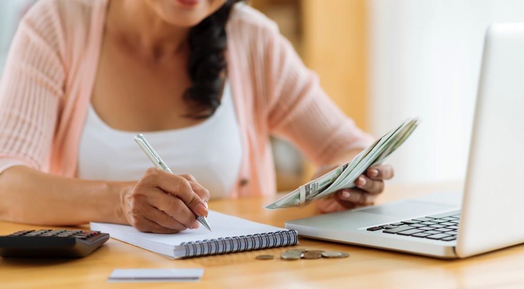 Mujer revisando sus finanzas con libreta y laptop