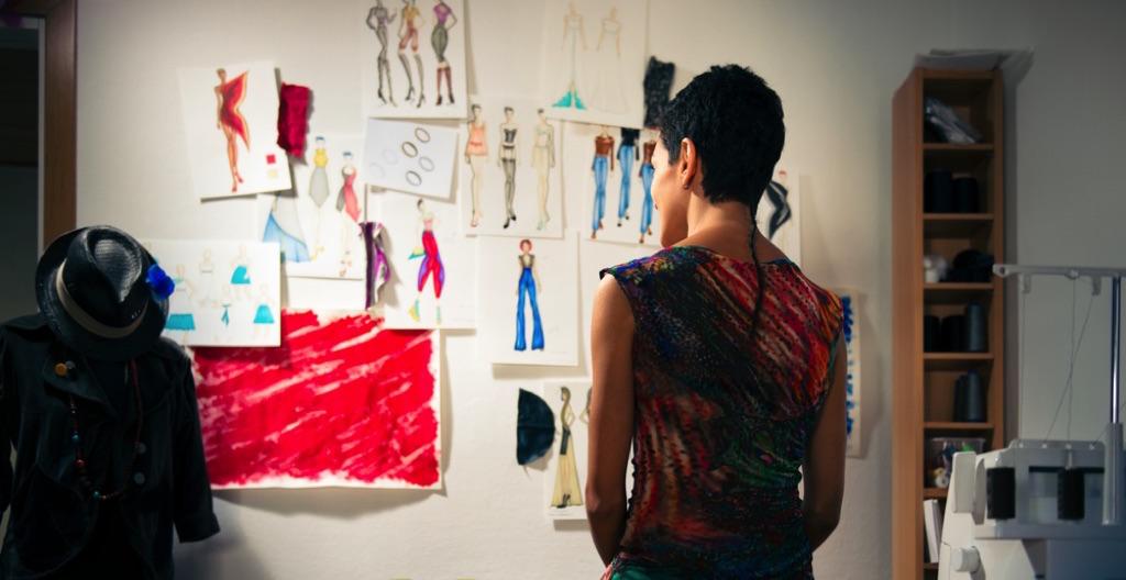 Chica viendo sus diseños en una pared