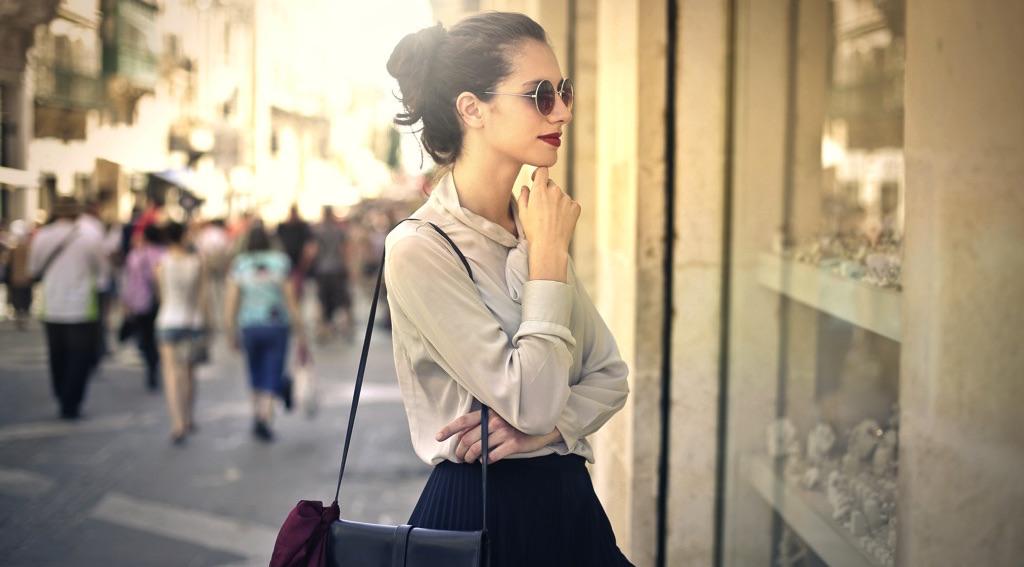 Chica viendo ropa en una vitrina