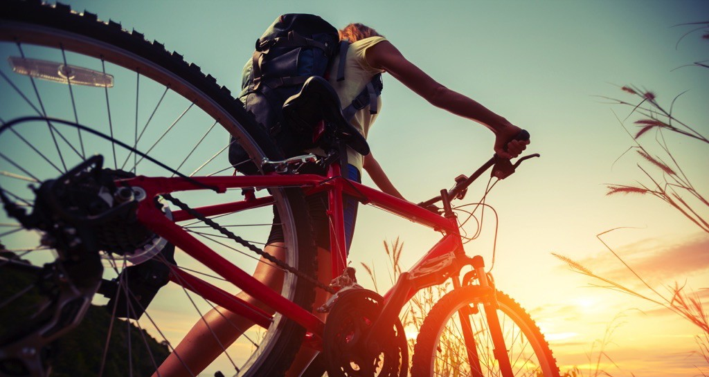 Mujer con mochila junta a su bicicleta
