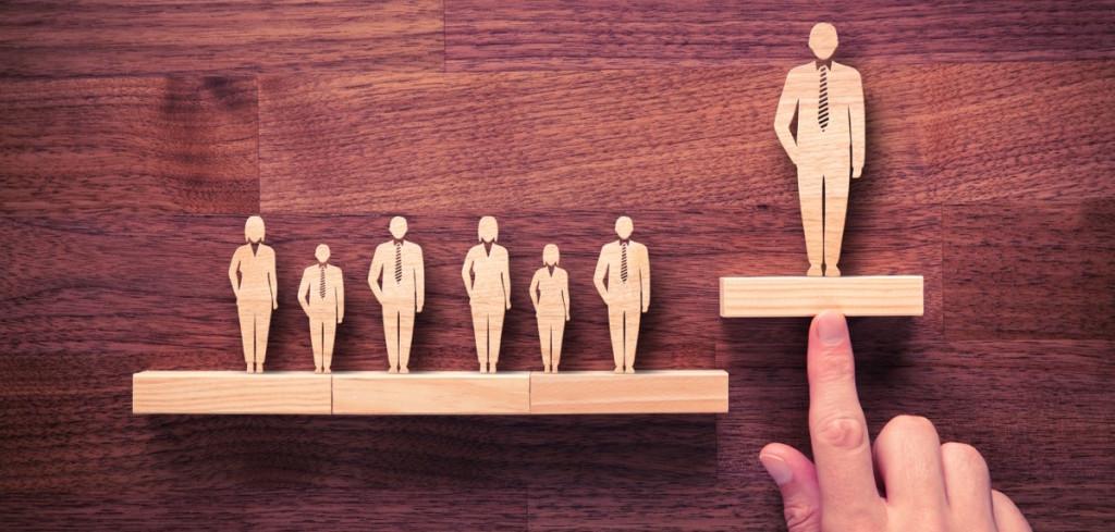 Personas de madera, una persona destaca sobre el resto