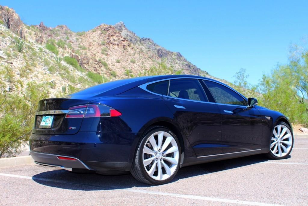 Parte posterior de un Tesla color azul en un fondo de montañas