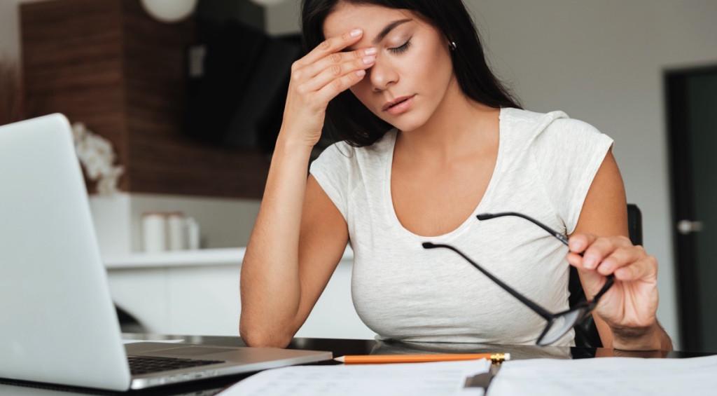 Mujer estresada frente a una laptop