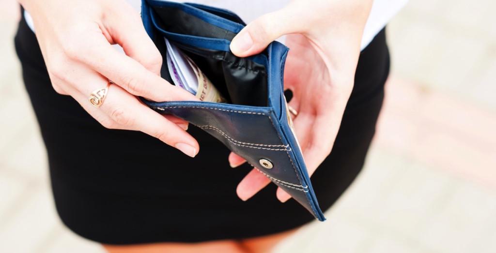 Mujer viendo su billetera con dinero