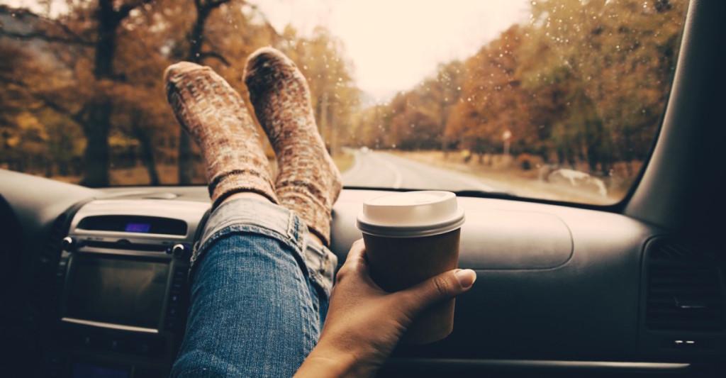persona tomando café en su auto