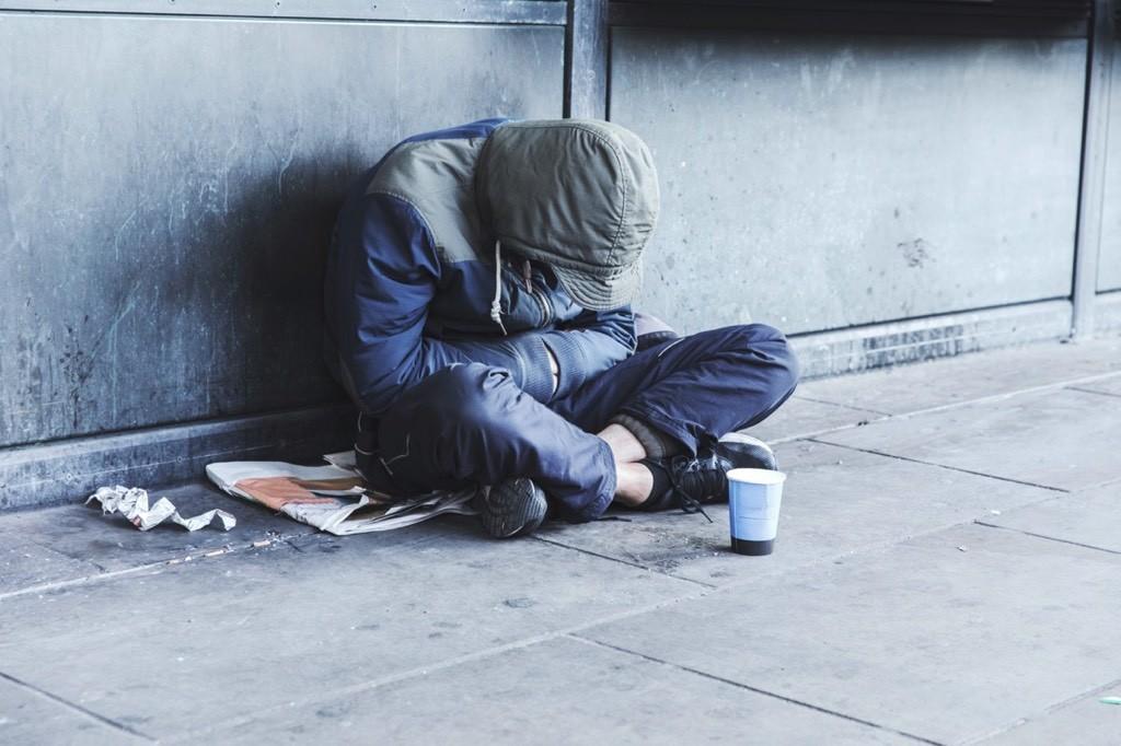 Chico pobre sentado en la calle